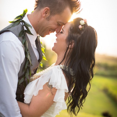 Groom with a mohawk clutches his dark haired bride in Launiapoko, Maui.