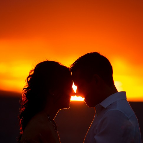 silhouette of bride and groom touching noses as the sun sets in the horizon.